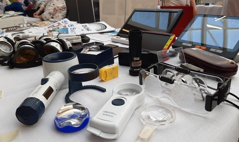 Fotografia, na ktorej sú zobrazené rôzne optické a kompenzačné pomôcky, spolu s informačnými materiálmi o problematike zrakového postihnutia